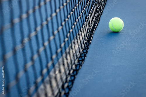 Tennis Ball next to a Tennis Net