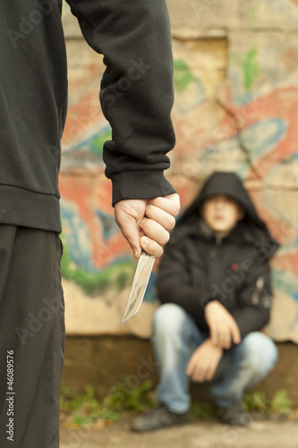 Boy looks at a man with a knife