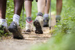 shoes of people trekking in wood and walking in row