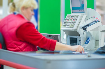 Cash-desk with cashier and terminal in supermarket. Serve custom