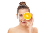 Woman holding orange over eye
