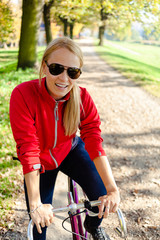 Happy woman cycling on bicycle, autumn in city