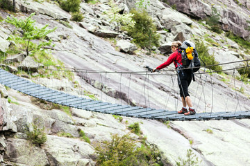 Woman trekking with backpack crossing bridge
