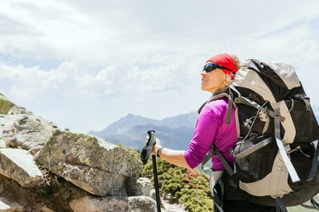 Woman hiking with backpack in mountains, France