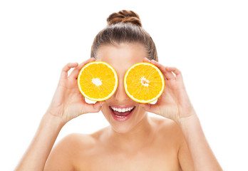 Woman holding oranges over eyes