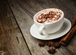 canvas print picture - coffee cup and beans, cinnamon sticks, nuts and chocolate on woo