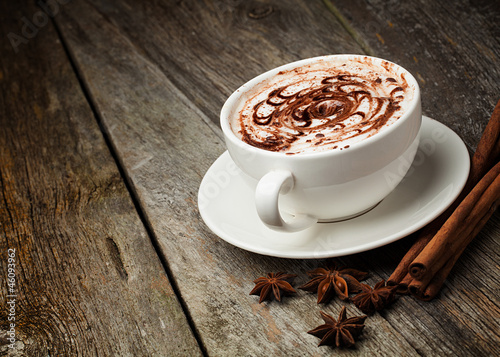 coffee cup and beans, cinnamon sticks, nuts and chocolate on woo