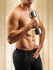 a muscular male torso with dumbbell