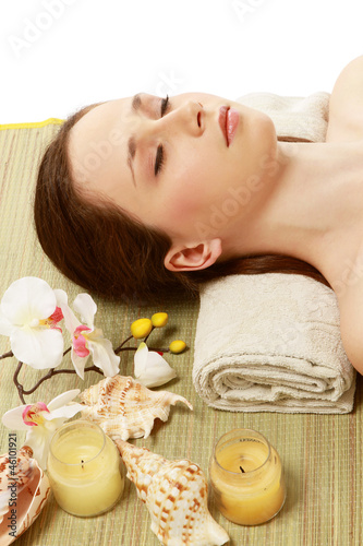 A young woman is lying during a spa treatment on a towel