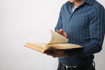 Male hands are browsing through the open book