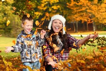 Mutter und Kind spielen im Herbstlaub