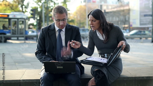 Angry business couple with laptop and documents in the city, ste