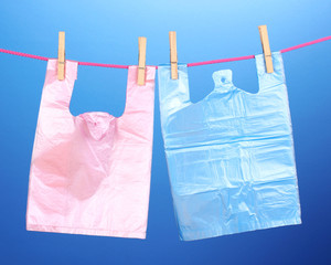 Cellophane bags hanging on rope on blue background
