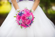Bride hands holding pink wedding bouquet closeup