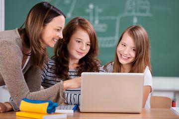 lehrerin erklärt schülern etwas am laptop