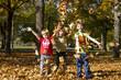 Kinder spielen im Laub
