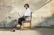 ritratto di giovane ragazzo seduto su una sedia in esterno