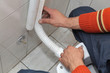 Plumber fix plastic tube, of wall mounted toilet cistern