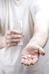 Caring man bringing pill and water