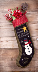 Christmas stocking with presents on wood