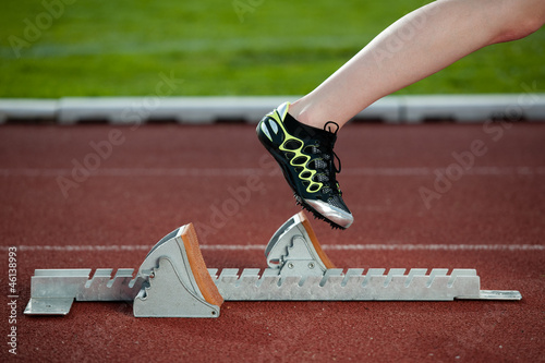 Female sprinter leaving the starting blocks