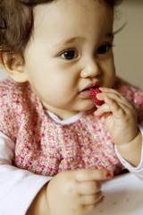 Bambina mangia una fragola