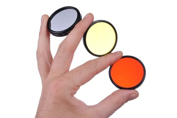 man hand holds three photographic filters, isolated on white