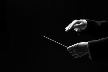 Hands of a conductor isolated on black background