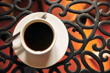 Black coffee on curved steel table