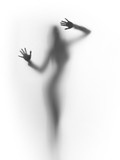 diffuse silhouette of a slim lady, behind a glass surface