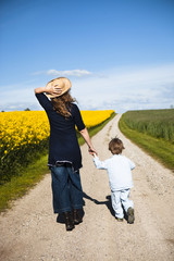 Mother and son walking on a path through yellow fields