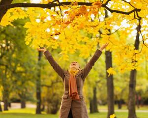 Happy woman throwing fallen leaves