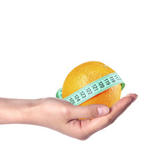 Woman's hand holding orange with measuring tape
