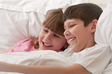 Smiling children in bed playing. Close-up.