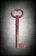 Old rusty key isolated on grunge background.