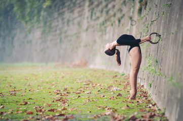 Young beautiful ballerina dancing in Tevere riverside in Rome.