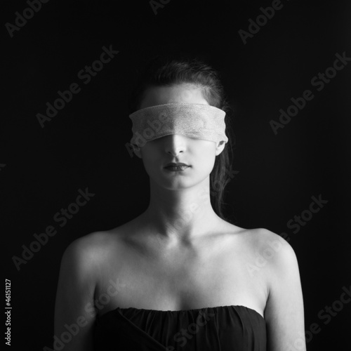Close up of woman constrained by gauze ring on eyes.