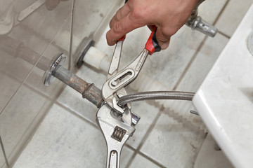 Plumber fixing water pipe of tap on bidet in washroom