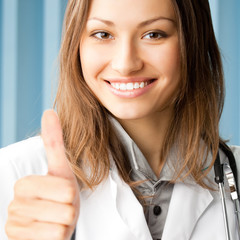Young female doctor with thumbs up gesture