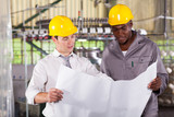 factory manager and worker looking at production plan