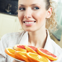 Cheerful woman with plate of oranges and grapefruit