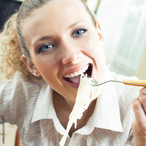 Cheerful woman eating spaghetti