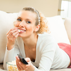Smiling woman watching TV at home