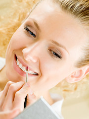 Cheerful smiling woman applying lipstick