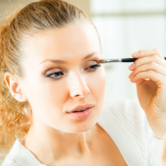 Cheerful smiling woman with mirror and makeup brush