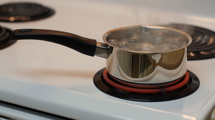 Pot full of boiling water on the electric stove.