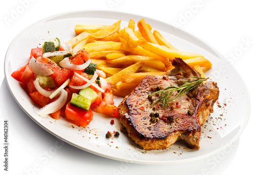 Grilled steaks, French fries and vegetables