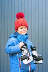 Kind mit roter Mütze hat Schlittschuhe