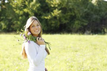 Hübsche dunkelhaarige Frau mit Sommerblumen