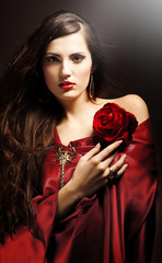 attractive woman in red drapery with red rose